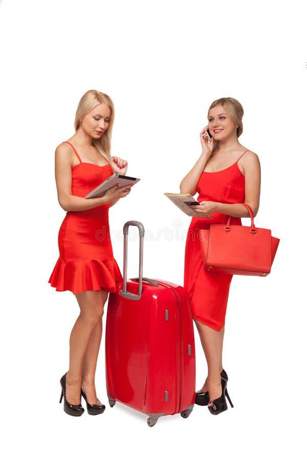 Due ragazze che indossano il rosso si veste con la grandi valigia e borsa e tabl immagini stock