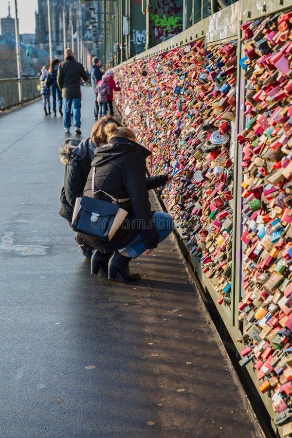 Due ragazze che osservano le serrature di amore in Colonia Koln Germania immagini stock libere da diritti