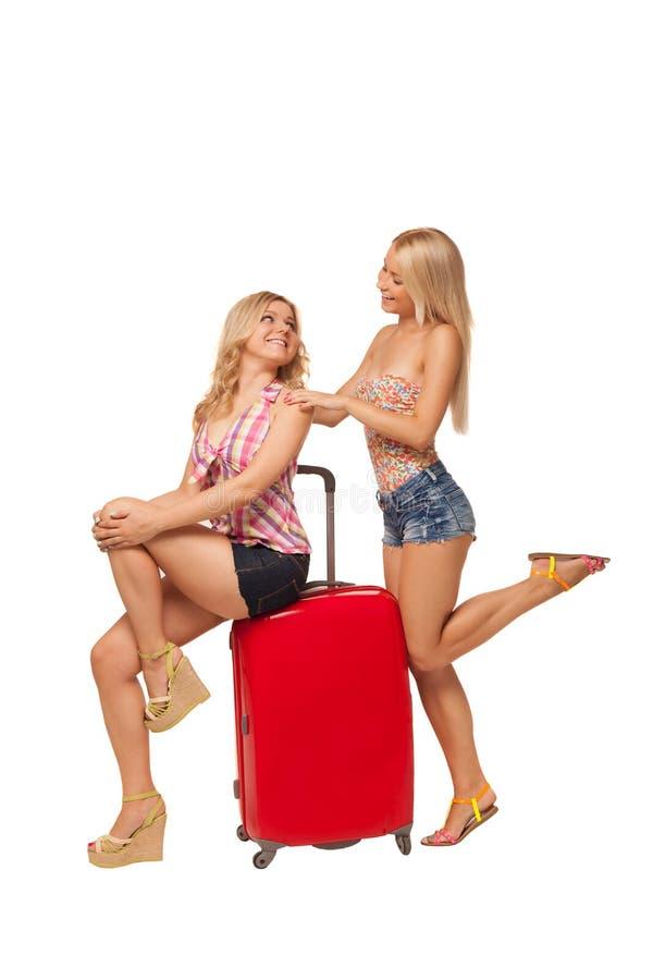 Due ragazze che portano i jeans mette con la grande valigia rossa fotografia stock