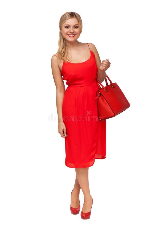 Due ragazze che portano i jeans mette con la grande valigia rossa fotografie stock