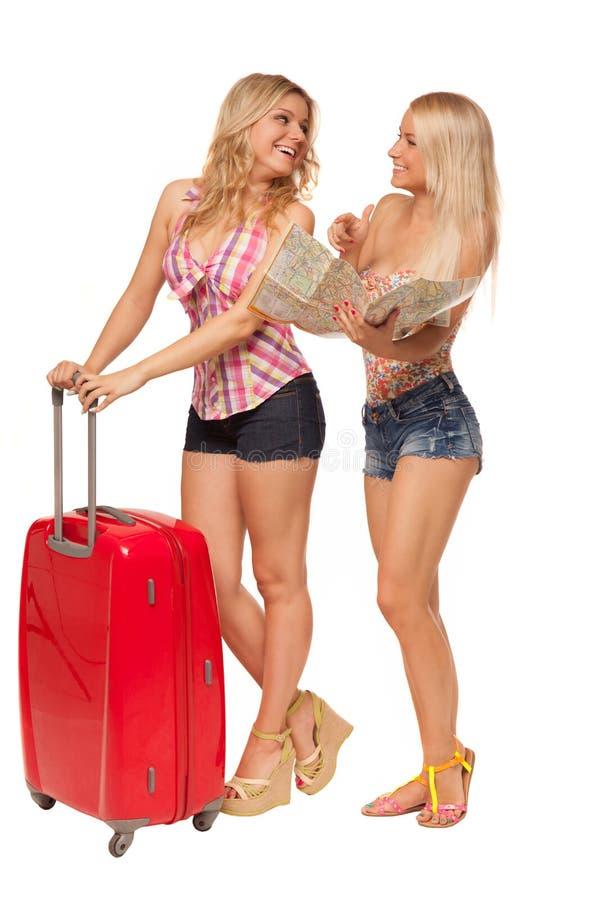 Due ragazze che portano i jeans mette con la mappa e la valigia rossa fotografie stock libere da diritti
