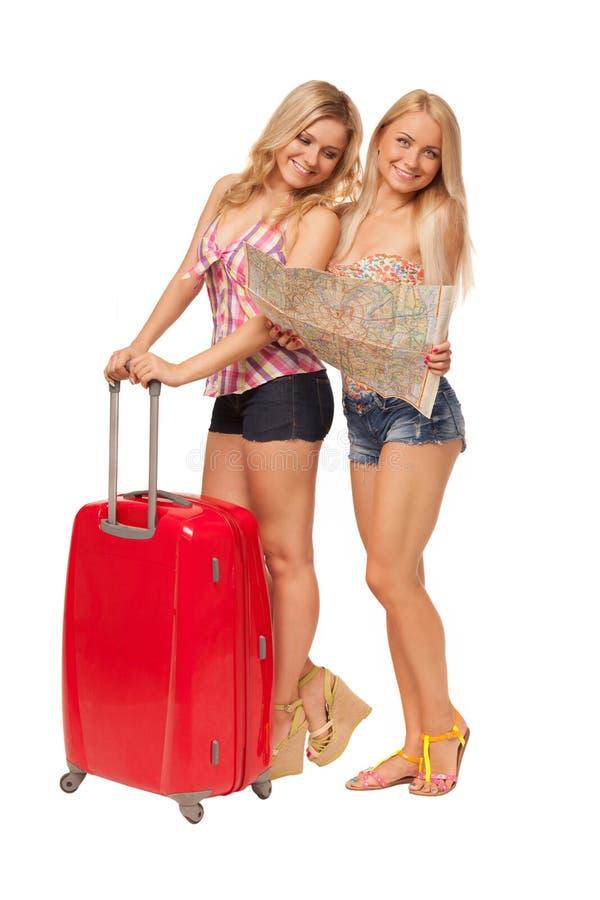 Due ragazze che portano i jeans mette con la mappa e la valigia rossa fotografia stock libera da diritti