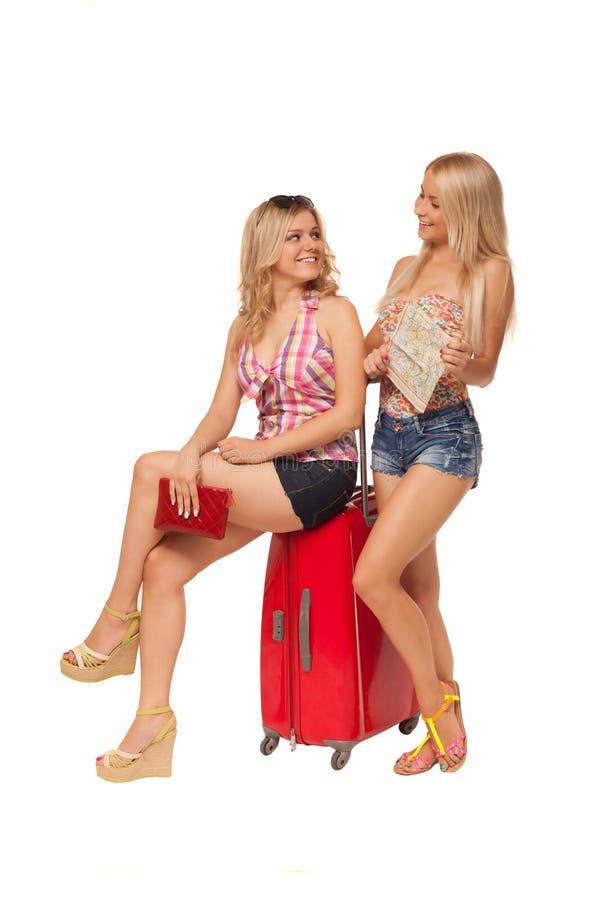 Due ragazze che portano i jeans mette con la mappa e la valigia rossa fotografia stock