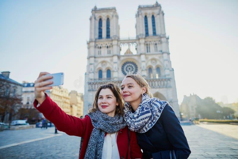 Due ragazze che prendono selfie vicino a Notre-Dame a Parigi fotografie stock