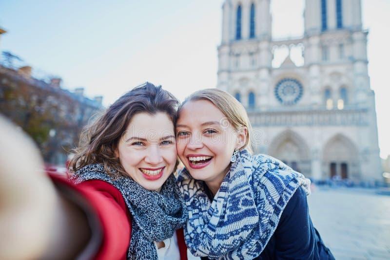Due ragazze che prendono selfie vicino a Notre-Dame a Parigi fotografie stock libere da diritti