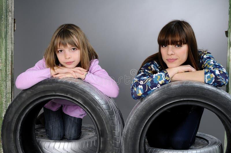 Due ragazze che propongono sulle gomme fotografia stock