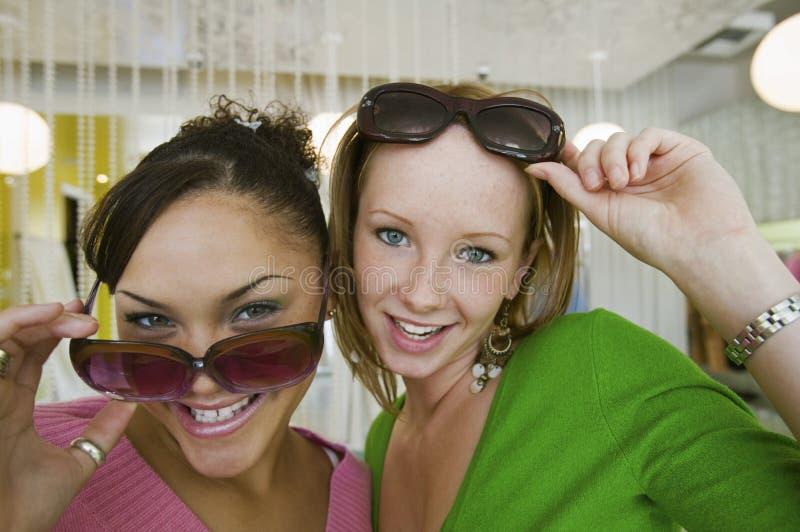 Due ragazze che provano sugli occhiali da sole nella fine del ritratto del boutique su fotografia stock libera da diritti