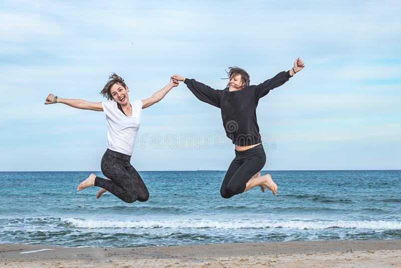 Due ragazze che saltano sulla spiaggia immagine stock