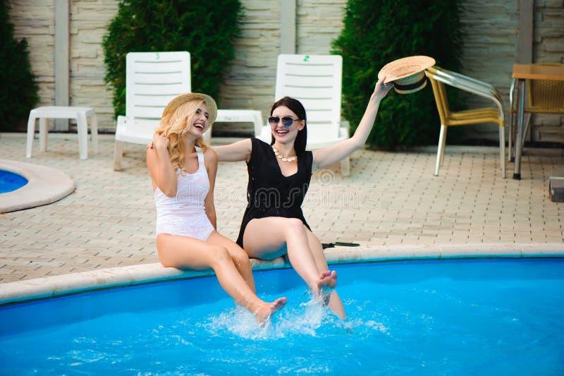 Due ragazze che si rilassano vicino all'acqua sulla vacanza fotografie stock