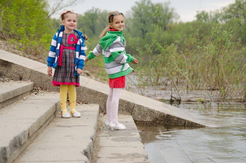 Due ragazze che stanno sui punti si avvicinano all'acqua immagine stock