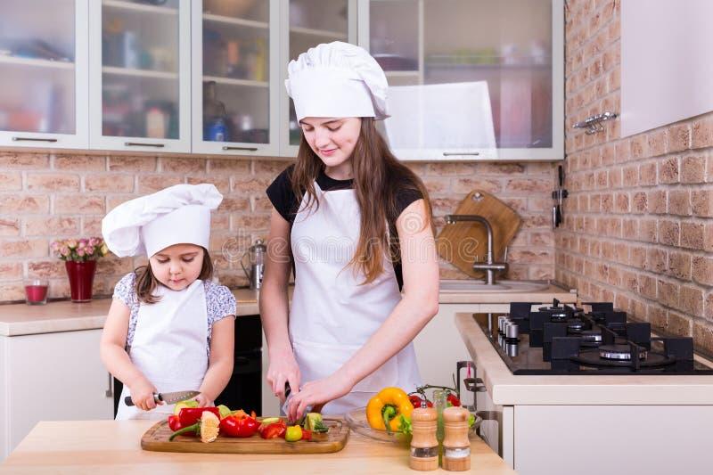 Due ragazze che tagliano gli ortaggi freschi crudi per cucinare fotografie stock libere da diritti