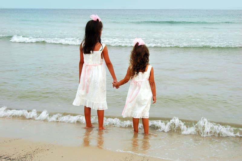 Due ragazze che tengono le mani fotografie stock