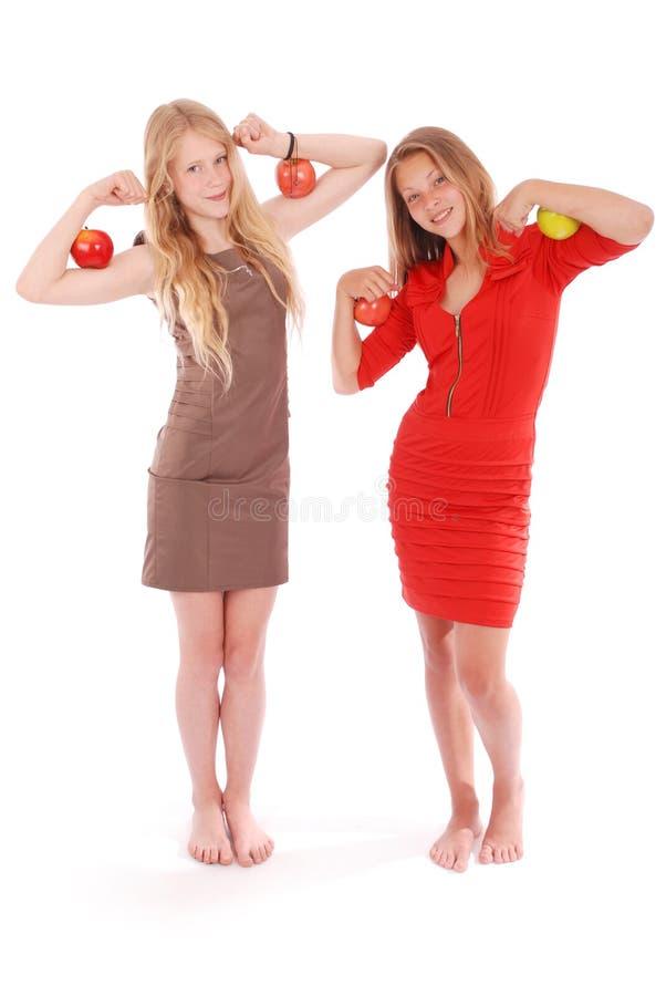 Due ragazze che tengono le mele sui suoi bicipiti immagine stock libera da diritti