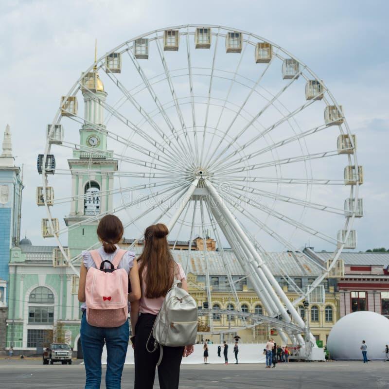 Due ragazze con gli zainhi che esaminano la ruota panoramica, vista posteriore, nella città fotografie stock