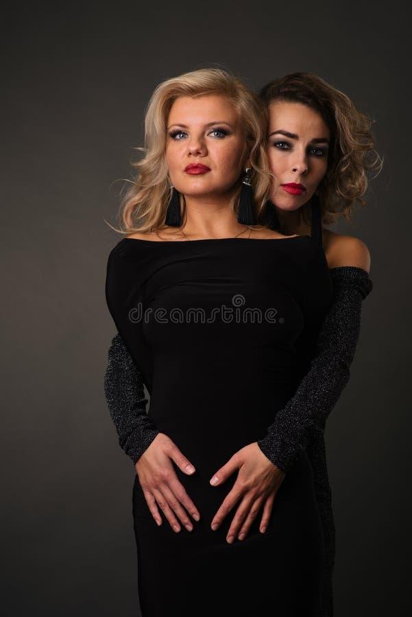 Due ragazze con le cicatrici dell'acne sul loro fronte Modelli che posano su un fondo scuro fotografia stock
