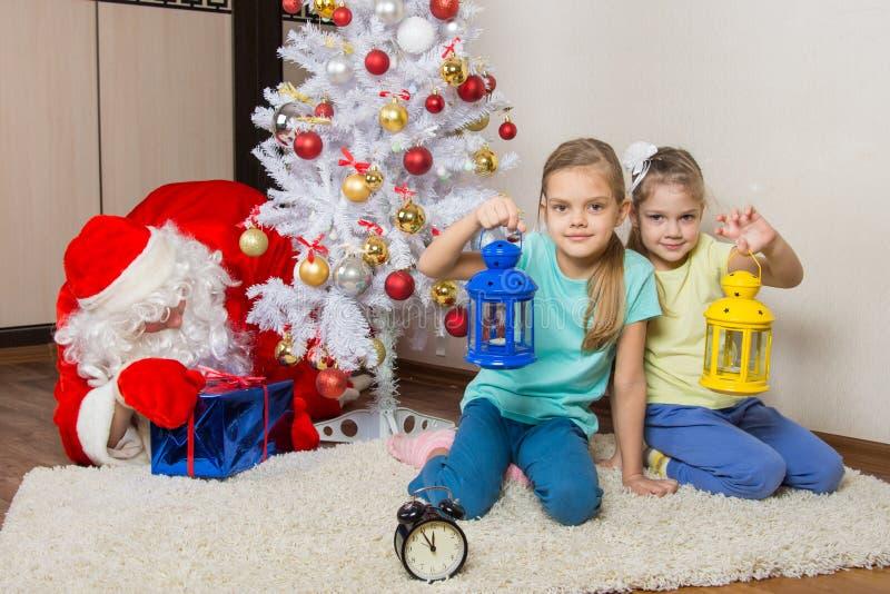 Due ragazze con le torce elettriche che aspettano Santa Claus all'albero di Natale durante i nuovi anni EVE immagini stock libere da diritti