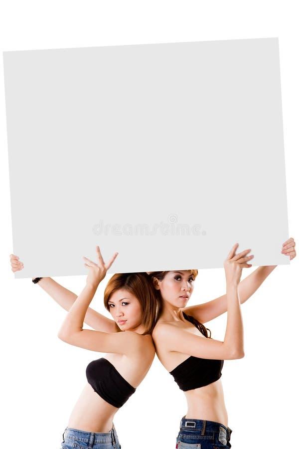 Due ragazze con un grande segno immagine stock