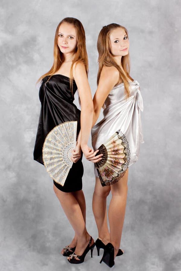 Due ragazze con un ventilatore in capi. fotografia stock