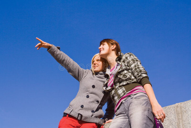 Due ragazze contro cielo blu fotografia stock