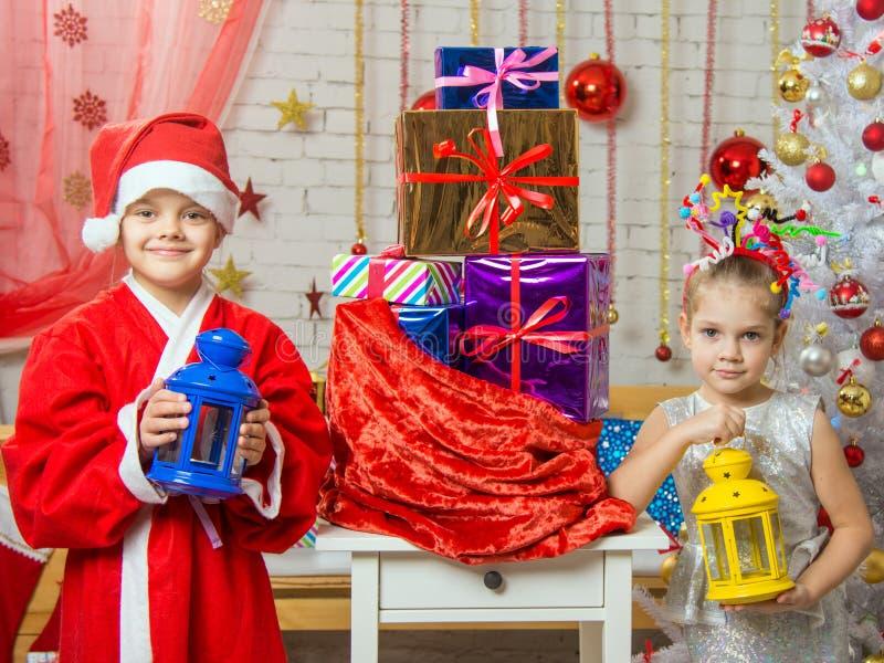 Due ragazze in costumi di Natale sono con i candelieri dalla borsa con i regali di Natale immagine stock