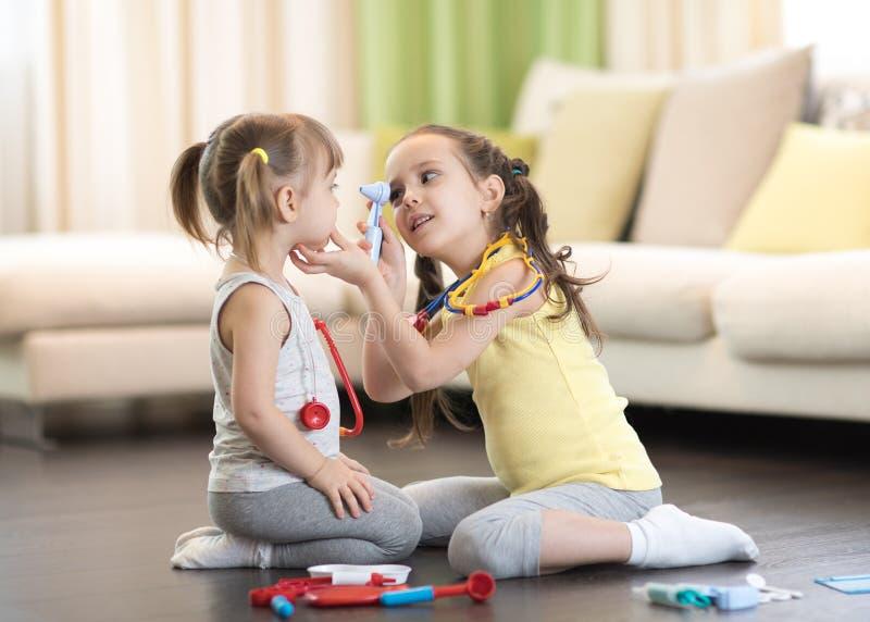 Due ragazze dei bambini che giocano al dottore nel salone fotografie stock libere da diritti