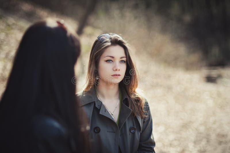 Due ragazze di fronte ad a vicenda in un parco di autunno fotografia stock libera da diritti