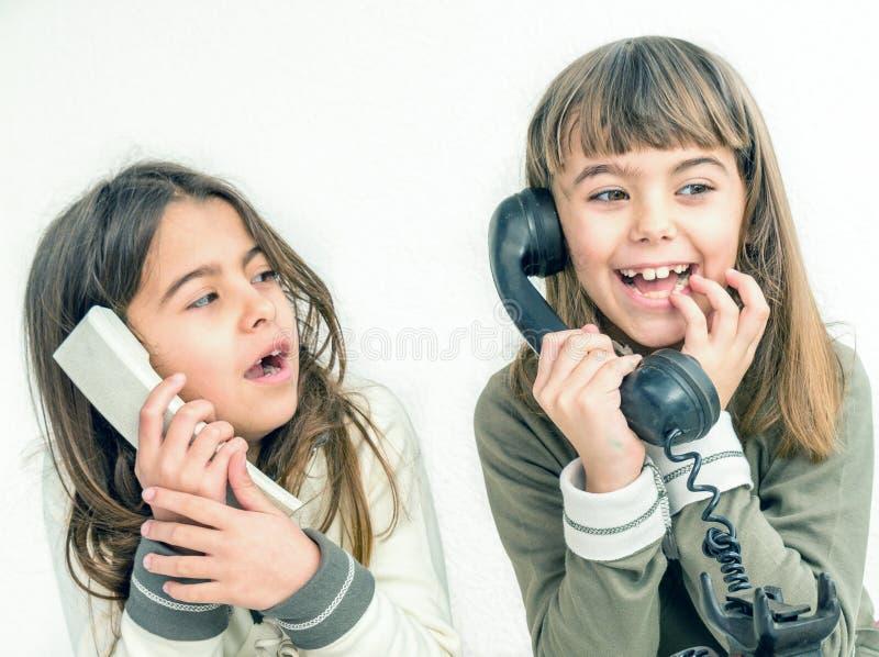Due ragazze di sette anni che parlano sui vecchi telefoni d'annata con fotografie stock