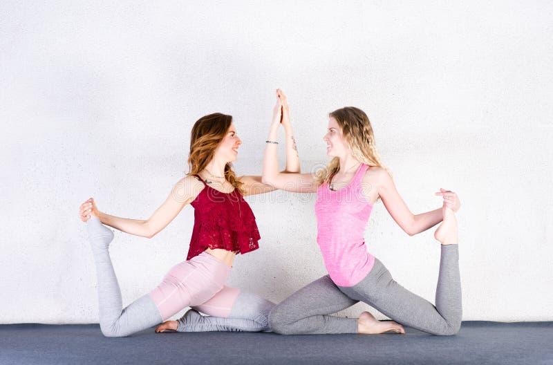 Due ragazze di sport preparano l'yoga in una classe di forma fisica Gruppo di allungamento delle giovani donne fotografie stock libere da diritti