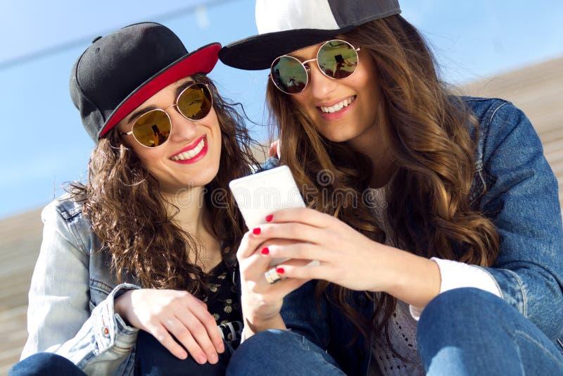 Due ragazze divertendosi con gli smartphones fotografia stock libera da diritti