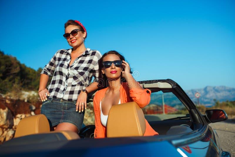 Due ragazze divertendosi nel cabriolet all'aperto fotografie stock