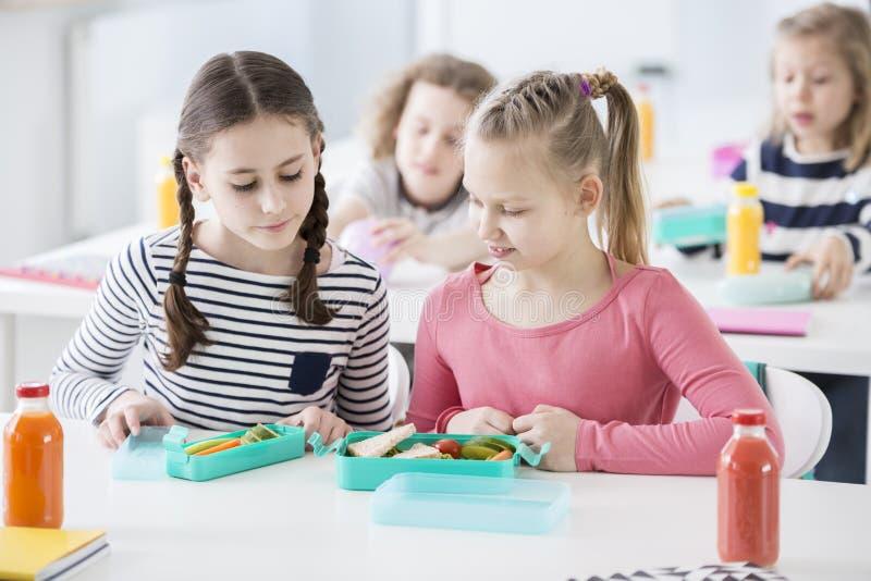 Due ragazze durante il tempo dello spuntino in una scuola che esaminano ciascuno immagini stock libere da diritti