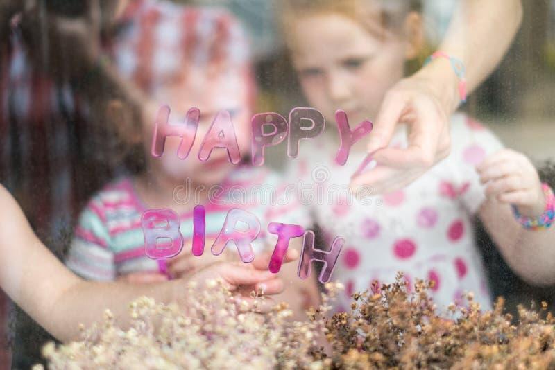Due ragazze (4 e 5) compleanno del bastone il buon segnano la t con lettere immagini stock
