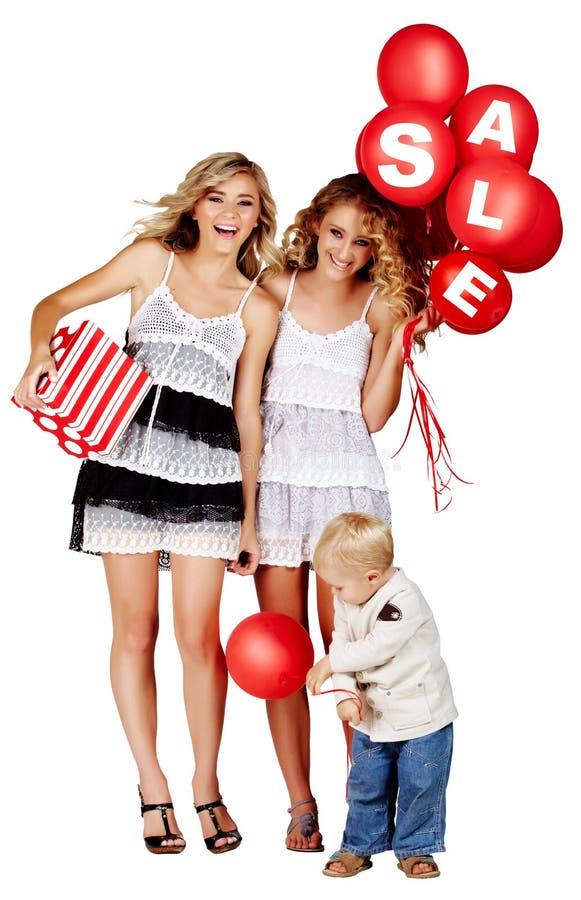 Due ragazze e un ragazzino con il segno di vendita immagine stock