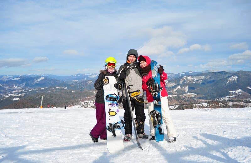 Due ragazze e una condizione del ragazzo e snowboads della tenuta fotografia stock libera da diritti
