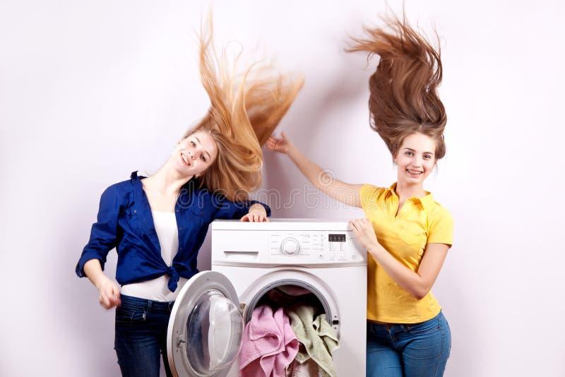Due ragazze e una lavatrice su fondo bianco fotografia stock libera da diritti