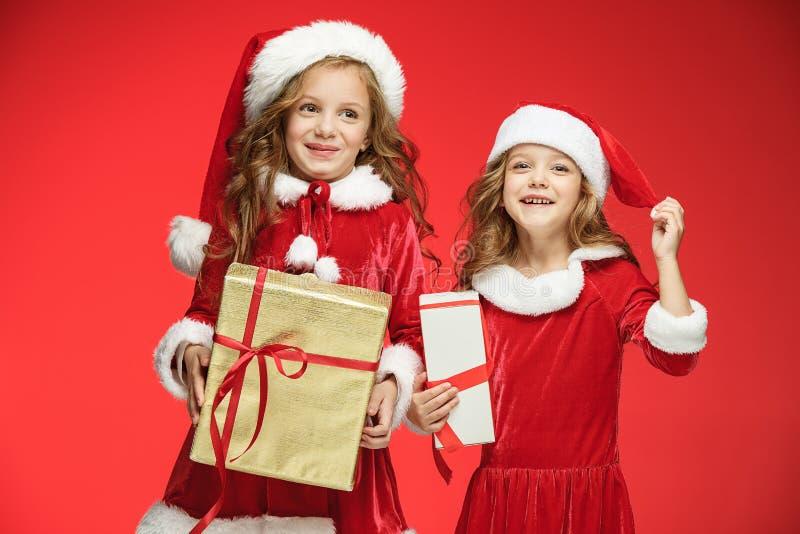 Due ragazze felici in cappelli del Babbo Natale con i contenitori di regalo fotografia stock