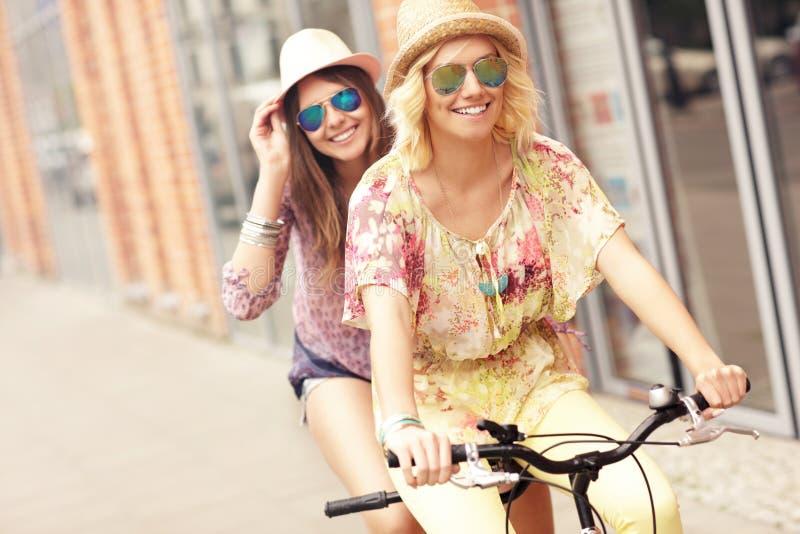 Due ragazze felici che guidano bicicletta in tandem fotografia stock