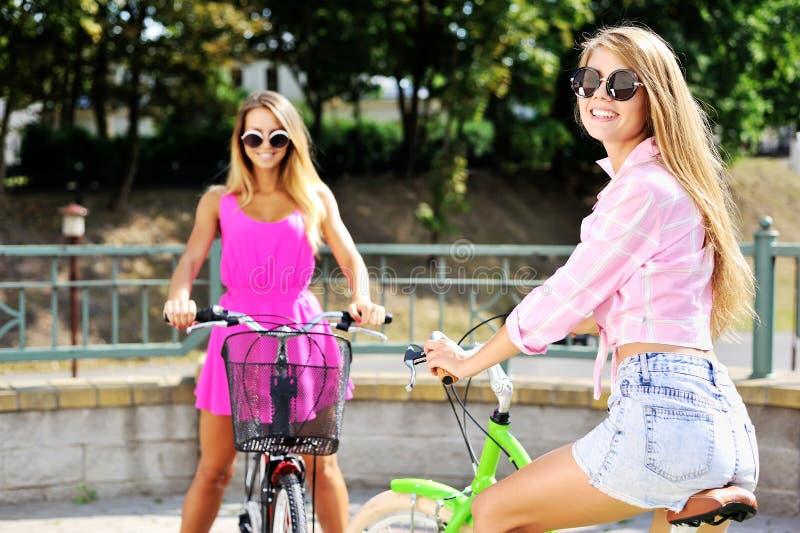 Due ragazze felici con le biciclette fotografie stock