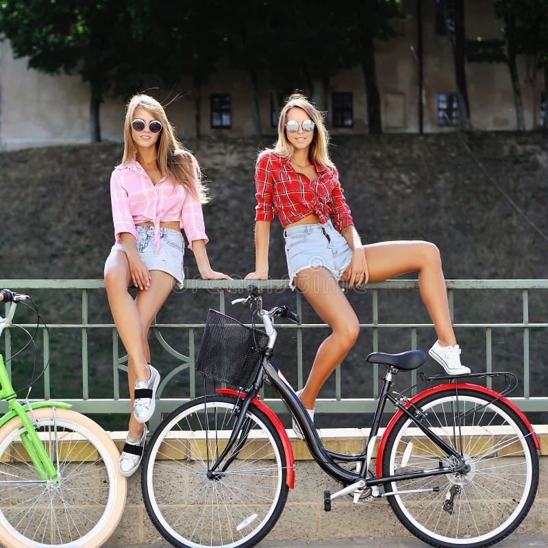 Due ragazze felici con le biciclette immagini stock