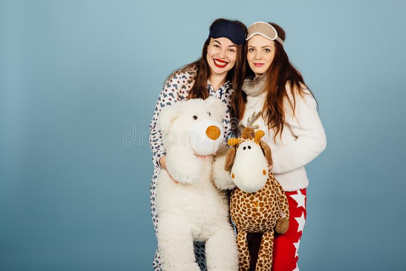 Due ragazze felici in pigiami tengono i giocattoli in loro mani fotografia stock libera da diritti