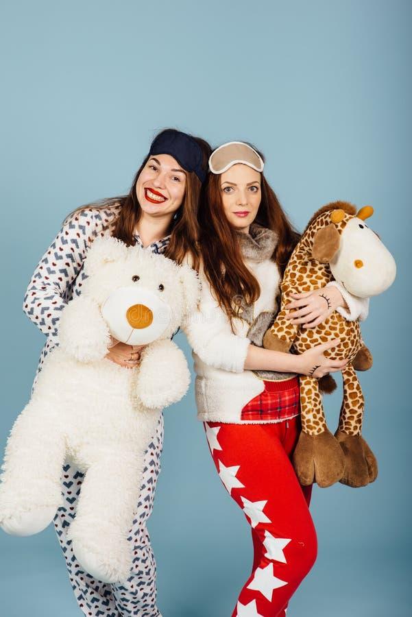 Due ragazze felici in pigiami tengono i giocattoli in loro mani fotografie stock libere da diritti