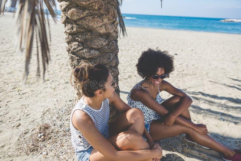 Due ragazze graziose che si siedono insieme sulla spiaggia immagini stock libere da diritti