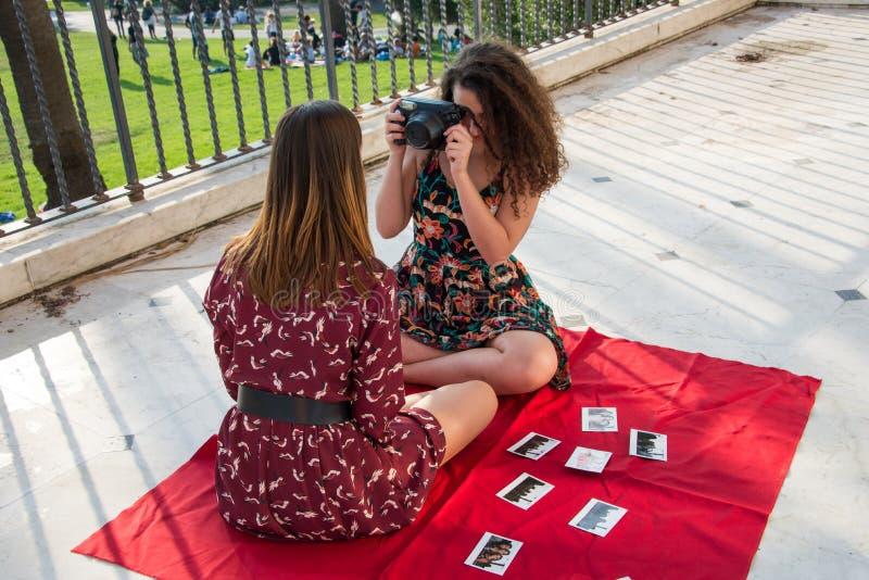 Due ragazze graziose stanno prendendo le foto per i media sociali fotografia stock
