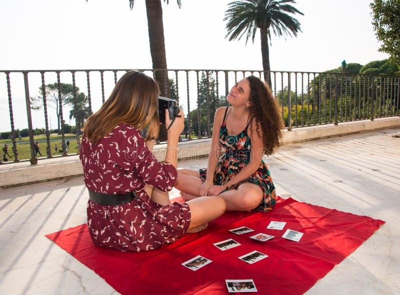 Due ragazze graziose stanno prendendo le foto per i media sociali fotografia stock libera da diritti