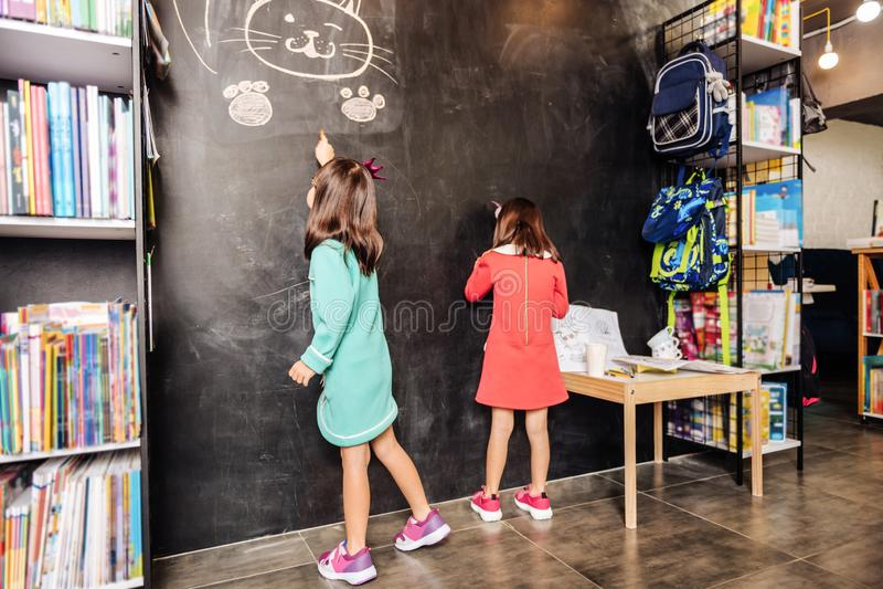 Due ragazze more che portano i vestiti luminosi che stanno alla lavagna fotografia stock