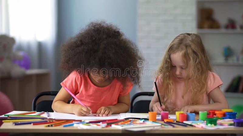 Due ragazze multi-razziali che disegnano con le matite variopinte nel centro per l'educazione in anticipo fotografie stock