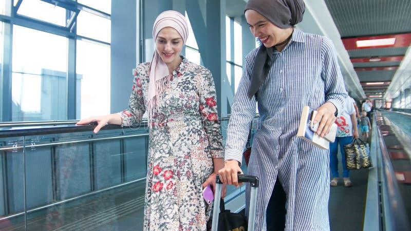 Due ragazze musulmane sul modo alla fine dell'aeroporto su fotografie stock