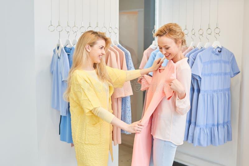 Due ragazze in negozio di vestiti immagini stock libere da diritti