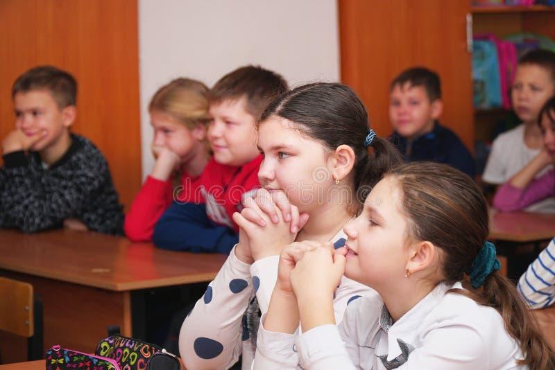 Due ragazze nell'aula che ascoltano l'insegnante immagine stock libera da diritti