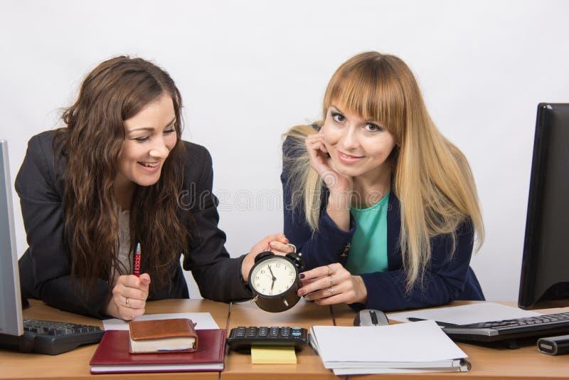 Due ragazze nell'ufficio che aspetta felicemente la conclusione del giorno lavorativo fotografia stock